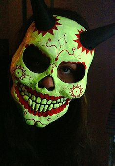 """Submitted by necrowafer.  """"Indian Summer Demon"""" Dia de los Muertos mask papier mache cast by hand from an original mold, hand painted, embellished with black papier mache horns. The green paint is glow in the dark and UV/blacklight sensitive.Ready to wear or be displayed aswall art.If you're interested in purchasing ($30 not including shipping - masks on Etsy similarly priced aremanufactured papier mache) get at me at Shufflebored@aol.com."""