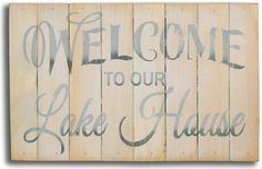 """Welcome guests to your the Lake House with this 8""""x12"""" off white washed slat beach sign with hand painted lettering """"Welcome to Our Lake House""""."""