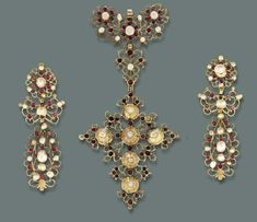 AN ANTIQUE GARNET AND PEARL DEMI-PARURE   The pendant of openwork cruciform design to the baroque pearl and garnet surround, a pair of ear pendants en suite (pearls untested), late 18th century, pendant 15.3 cm. high, ear pendants 9.7 cm. high