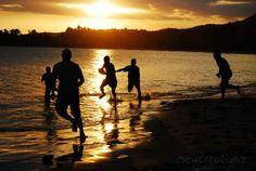 Sunset in Fiji with silhouette football players in by NewCreatioNZ