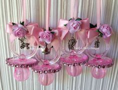 """Greet your guest with one of these beautiful pacifier. These fancy pacifiers are perfect as baby shower favors and a """"Don't Say Baby"""" game. The necklace is decorated with the charm of your choice . Each pacifier measures 2.75"""" long. Have two-sided bow."""