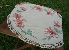 Lovely linen table topper with hand stitched poinsettias all around. Nostalgic look of oatmeal colored fabric with muted reds and pinks for petals and different shades of green for the leaves. the centers are made with knots that give a multi dimensional affect, using black and yellow