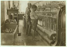 Doffers in Cherryville Manufacturing Company,  N.C.   When the bobbins on the spinning machines were full of thread, doffers removed the full bobbins and replaced them with empty ones. Here, doffers are working at a spinning machine in a mill in Cherryville. Behind them are carts of full and empty bobbins. Lewis Wickes Hine, photographer. From the records of the United States National Child Labor Committee.