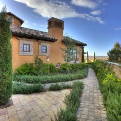 Rosemary creates a scented green border against the stone paths in this Tuscan Kathleen Vrizard garden.