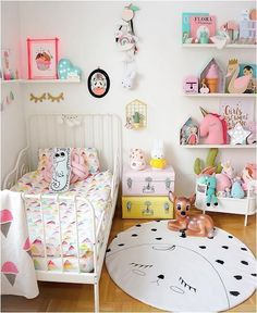 What a sweet room for a little girl. I love the vintage toys and eclectic colors. Toddler room decor perfection!