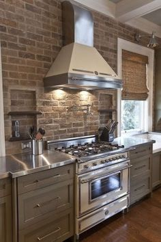 Warm and Rustic Kitchen - Stainless Steel Counter tops, exposed brick back splash, hood, bamboo window shades. by AislingH