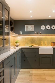 This L-shaped shaker style kitchen is painted in Farrow & Ball Down Pipe. The Concreto Biscotte worktop and brushed brass splashback add a fun, contemporary twist. The floating oak shelf adds movement through the space while the LED lights and glazed cabinet add light to compensate for lack of natural light. Hidden is an integrated pull out bin for convenience. The Classic Belfast under mounted sink and Perrin & Rowe Mayan tap add some tradition.