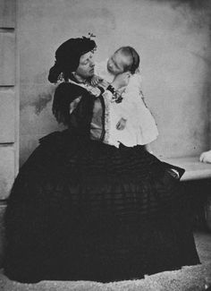 Photograph of a full length portrait of Queen Victoria seated on a bench. Princess Beatrice stands on the bench beside her mother. Queen Victoria touches Princess Beatrices cheek and looks at her daughter.