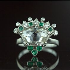 Rose Cut Diamond Platinum Crown Ring.  A one-of-a-kind fancy rose-cut diamond weighing approximately 1.50 carat has been creatively employed as the star of this majestic vintage crown (or coronet) ring. This unique treasure is further enhanced with emeralds and diamonds. Circa 1920's-1930's.