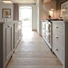 FARMHOUSE – INTERIOR – vintage early american farmhouse showcases raised panel walls, barn wood floor, exposed beamed ceiling, and a simple style for moulding and trim, like in this farmhouse neptune kitchen with a fantastic barnwood floor.