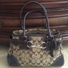 "SALE {Coach} Hampton's Brown Signature Satchel NEW LISTING! Authentic Hampton's Signature Coach Satchel/Shoulder Bag in brown with dark leather trim & handles. Silver hardware. This bag is pre-owned but in great condition. No rips, tears or stains. The only wear on the bag is on the outside corners where the leather has worn on both sides. Creed#: E06Q-10245. Measurements: 12"" (L) x 8"" (H). Strap Drop: 7""? Please keep in mind Poshmark takes 20%. ?? Coach Bags Satchels"
