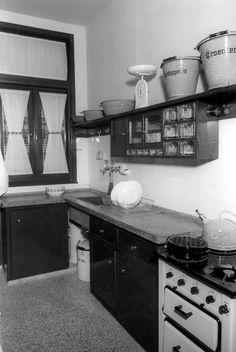 Keuken met fornuis, granieten aanrecht, emaille emmers en fluitketel. Rek met lades voor suiker, meel e.d., afdruiprek, afvalemmer, weegschaal. Plaats en datum onbekend.
