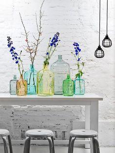 Des vases colorés de différentes tailles et formes et quelques branches fleuries.
