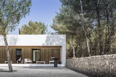 Designed by Spanish architecture firm Maria Castello Martinez, the Ca l´Amo House is a beautiful minimal property in the heart of a pine and juniper forest in Ibiza, Spain. Focusing on preserving the landscape intact as much as possible, the modern Spanish Architecture, Contemporary Architecture, Contemporary Homes, Wood Cladding Exterior, Dry Stone, Wood Laminate, Countryside, House Design, Landscape