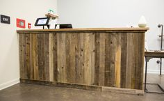"""Front Desk: Our friends replaced an old fence and gave us the naturally aged wood. We cut it into strips and installed them vertically to go with our """"Vertical Theme."""" Stained concrete floors gives a nice accent to the wood. Every detail matters to us. Our homemade toilet paper roll. We brought our industrial design to our restroom. Iron pipe with oak wood with oak weather stain. #diy #affordablebuilding #gonsteadchiro #industrial"""
