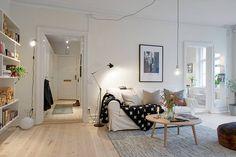 Długi szary kabel lampy-żarówki umożliwił upięcie jej tak, by znajdowała się dokładnie nad stolikiem kawowym. Współgra ona z kinkietem przy regale i czarną przegubową lampą podłogową. Wszystkie trzy zdobią białą ścianę wyrazistymi nieregularnymi liniami.