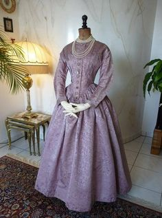 A mauve damask silk dress from the Romantic Period, ca. 1845. With radiating pleats from low V shaped waist, the bodice adorned with silk cord rosettes, fitted sleeves, hook and eye rear closure. Very good to excellent condition. Slight rubbing to 2 domed centres of rosettes at lower