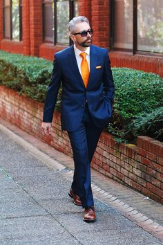 Keith is dashing in a navy suit with sporty orange accents.