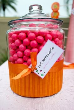 Fuchsia-colored yet 'pink lemonade' flavored candy arranged in a clear glass jar with decorative lid....bottom of jar decorated to resemble an orange cupcake.... so SWEET!
