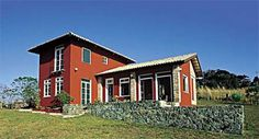 Na morada de 103 m², o telhado, a fachada colorida e o pátio de pedra rúst...