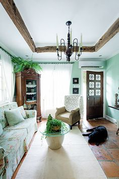 The front door opens up into a truly country hearth with Filipino pieces. Weathered wood panels suspended from the ceiling set the tone for other heavy wood pieces like the carved curio cabinet. It houses various ceramics and pipes. Household plants add a bit of living green to the scene.