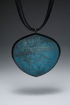 """Julia V. Turner     """"Blue Migration distressed wood pendant."""" In this piece the unspecified type of wood has been burned and stained. It's enclosed by steel and meticulously decorated with Japanese glass beads."""
