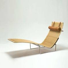 Poul Kjærholm, Denmark, 1965  PK 24 chaise lounge with frame of stainless steel, seat and back in cane, headrest in light brown leather. Produced by E. Kold Christensen. From R Gallery, NY.