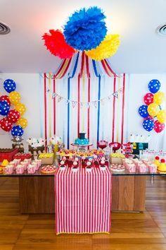 Uma tenda com fitas de cetim em cinco cores foi montada atrás da mesa do bolo pela decoradora Liliana Loureiro (www.lilianaloureiro.com.br) para uma festa com tema circo. Bandeirolas com as letras do nome do aniversariante foram aplicadas às fitas