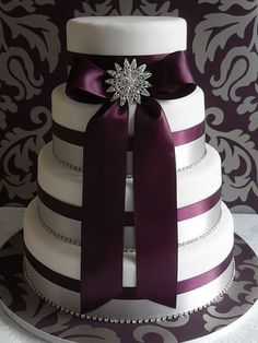 Love the ribbon centered on each tier to divide the subtle silver and white variance, plus the oversized bow with bling!