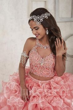 Saturated in chunky, AB rhinestones, this two-piece presents a bodice with an enchanting illusion neckline and beaded straps. The back of the bodice has brilliant rhinestone buttons and loops. The two