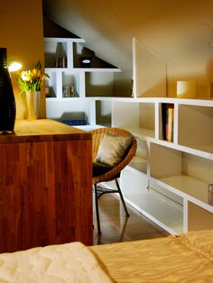 A desk tucked into a corner of a loft bedroom provides a quiet space to work, while surrounding shelves keep the space cozy and add an efficient storage solution