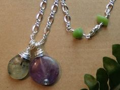 Jewelry by Merry Moonchild Soap Co.    Irises - Amethyst & Prehnite Necklace with Grass Turquoise Clasp    This necklace is inspired by the spring flowers growing outside my back door! :)    Wire Wrapped Amethyst and Rutilated Prehnite Necklace on silver plated chain with Grass Turquoise chips set into a handcrafted clasp. Total necklace length is 19 inches.