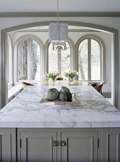 Kitchen carrera marble countertops - white cabinets, white trim, pewter Island, soft yellow walls