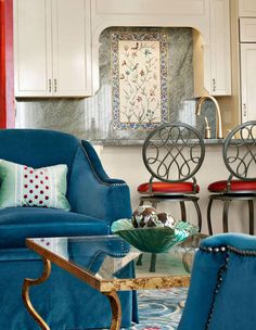 Living room decor with blue armchairs an wrought iron table in heavily antiqued gold leaf finish; red, blue and gold decor; living room decorating ideas