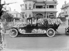 this is a picture of a 1920's hearse. back in the 1920s they had a different style of cars. they seemed to have thinner or no mirrors. this also came into the design of a hearse. hearses today. they are usually just one long car while this one resembles a small truck.