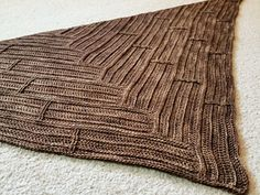 Parquet is a triangular scarf with a textured wooden pattern created using post stitches. It's worked in sections, with each section worked perpendicular to the last.
