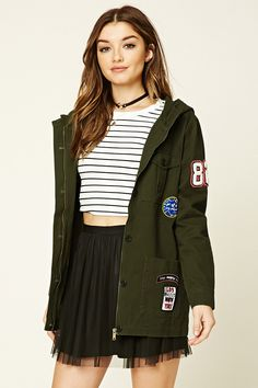 """A cotton jacket featuring front cargo pockets, """"4 Ever Young"""", """"Los Angeles/New York"""", """"Oops"""", """"Stop Judging Me"""" patches, a hood, long sleeves, a zip front with a button placket, and front patch pockets."""