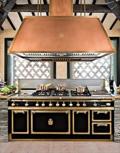Interesting how here they mixed copper in the hood with brass on the range. Interesting also that they used stacked stone, a more modern approach, with a less modern tile behind.