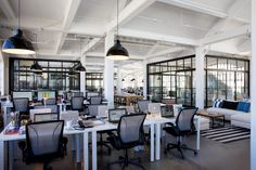 Office layout—The office is an open-concept layout - not even Jules, the founder of the company, has a private office. Even with conference rooms and designated work areas, the space is kept bright and open with glass walls and polished floors populated with clean rows of white desks and grey chairs.