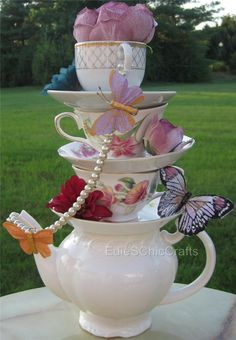 Planning a tea party themed event? Looking for the perfect gift for a friend who is a tea lover? This stacked teapot and teacup centerpiece is both unique and elegant.  With this centerpiece, you will receive a solid white or off-white teapot as the base, with three patterned teacups and three patterned saucers, all mismatched. They will be stacked, and glued permanently at a slight angle. Artificial flowers and beautiful butterflies dot the centerpiece, with a string of faux pearls draped…
