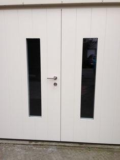 """Openslaande houten garagedeuren model """"Den Bosch"""" Dit mooie nieuwe model hebben wij in 2014 voor het eerst in Den Bosch geplaatst. Deurdikte 68mm Dark Red Meranti Loopdeur links of rechts openslaand (van buiten gezien) Deuren symmetrisch of 1/3-2/3 verdeling (zonder meerprijs) Deuren zijn voorzien van een zeer hoogwaardige isolatiekern voor een hele goede warmte-isolatie Rubber …"""