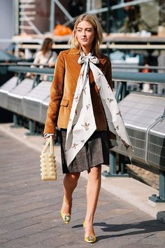 London fashion week street style spring 2018: Emili Sindlev in a  tan corduroy blazer, bow blouse, plaid skirt, yellow heels, and a shrimps bag