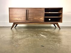 A classically styled mid-century modern credenza. Made with a mix of walnut, hardwood and veneer. Hand applied oil / poly satin finish. 3 adjustable shelves. Constructed out of high quality walnut hardwood and veneer on a pro core plywood (my reason for using some veneers instead of all solid wood, is its more eco friendly and theyre less prone to warping than solid wood. I build each unit the way I would build it for myself. All solid wood can be done as well). Dimensions 55 or 62 x 16.5 d…