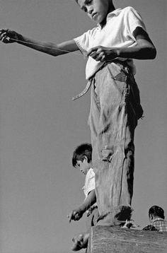 © Sergio Larrain/Magnum Photos CHILE. Taltal. Children fishing in the harbour. 1963.