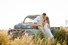 Outdoor wedding..picture taken in a field at sunset by a vintage Ford pickup truck