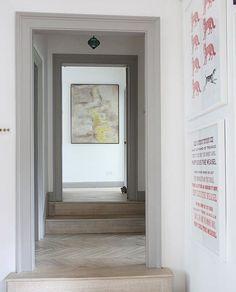 Artwork and herringbone wood floors in the upstairs hall