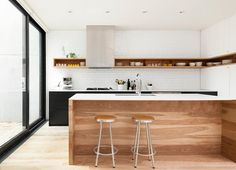 Love everything about this kitchen. The white painted brick wall, the matte black lower cabinets with white countertop