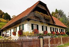 White ,austrian old village house in sumer time,with boxes with geraniums on windows and a wooden fence in foreground. Styria.
