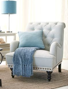 Chas Armchair from Pier 1. Nailhead trim and dark, carved wooden feet add even more character to the seersucker fabric.