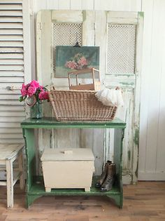 Shabby Chic vignette. Old door, wooden box, chair, aqua jar, roses, painting, baskets. Textures.